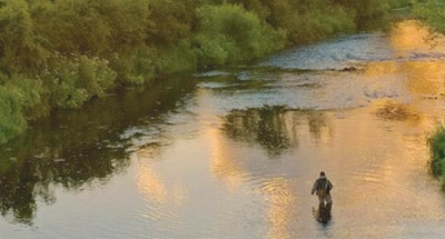 fisherman standing in river